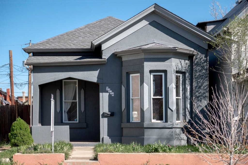 Starter home for sale in RiNo, Grey stucco with small porch