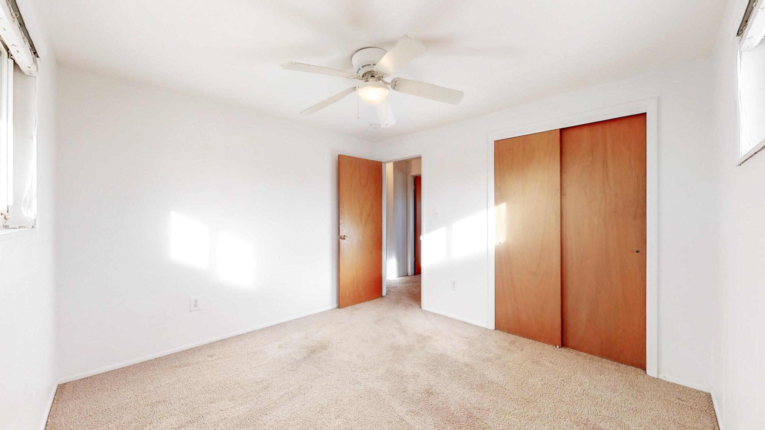 Medium Room, Brown Carpet, Closet With Wood Doors, Ceiling Fan