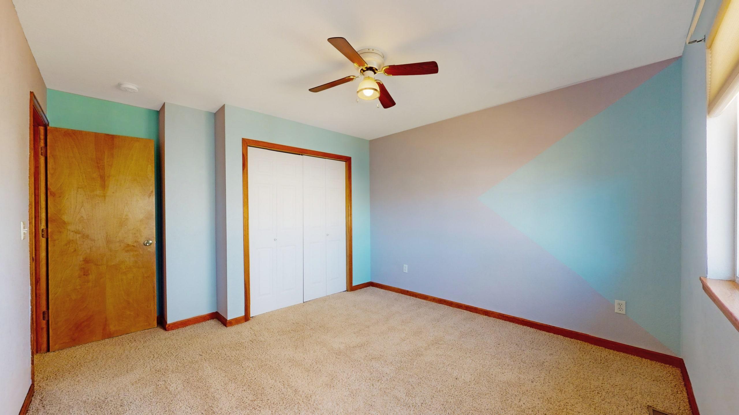 Bedroom with grey walls wood trim and white closet door beige carpet
