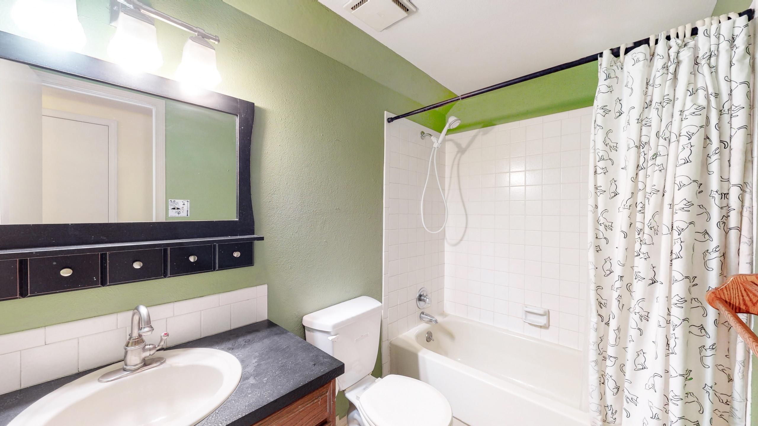 Brighton, CO home for sale, full bathroom, white tile tub, black vanity