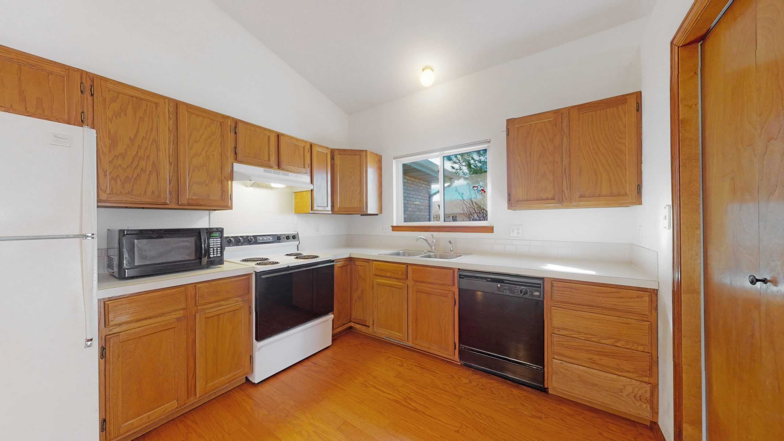 Brighton, CO house for sale with oak cabinets, white appliances, white walls