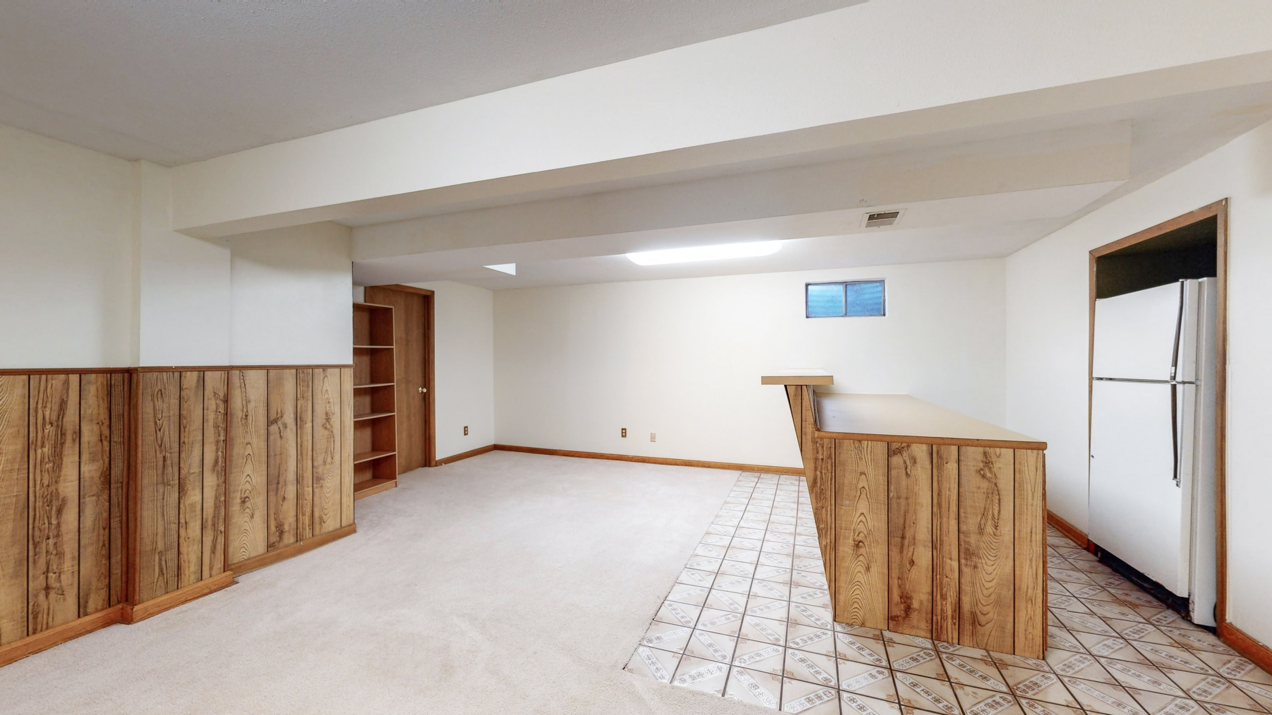 Brighton Home For Sale, basement with wood wainscoting and white walls