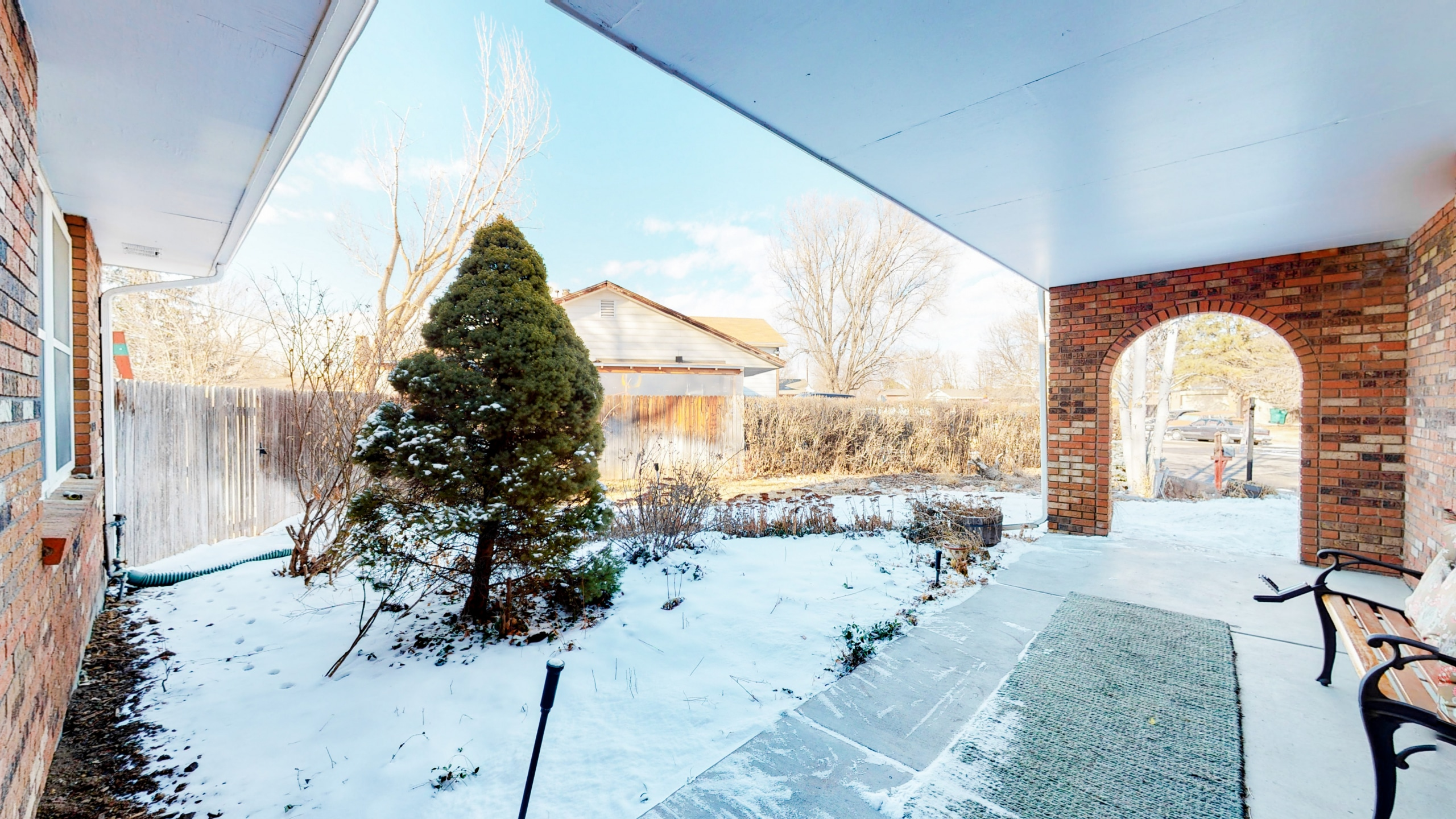 View of front covered patio, red brick home