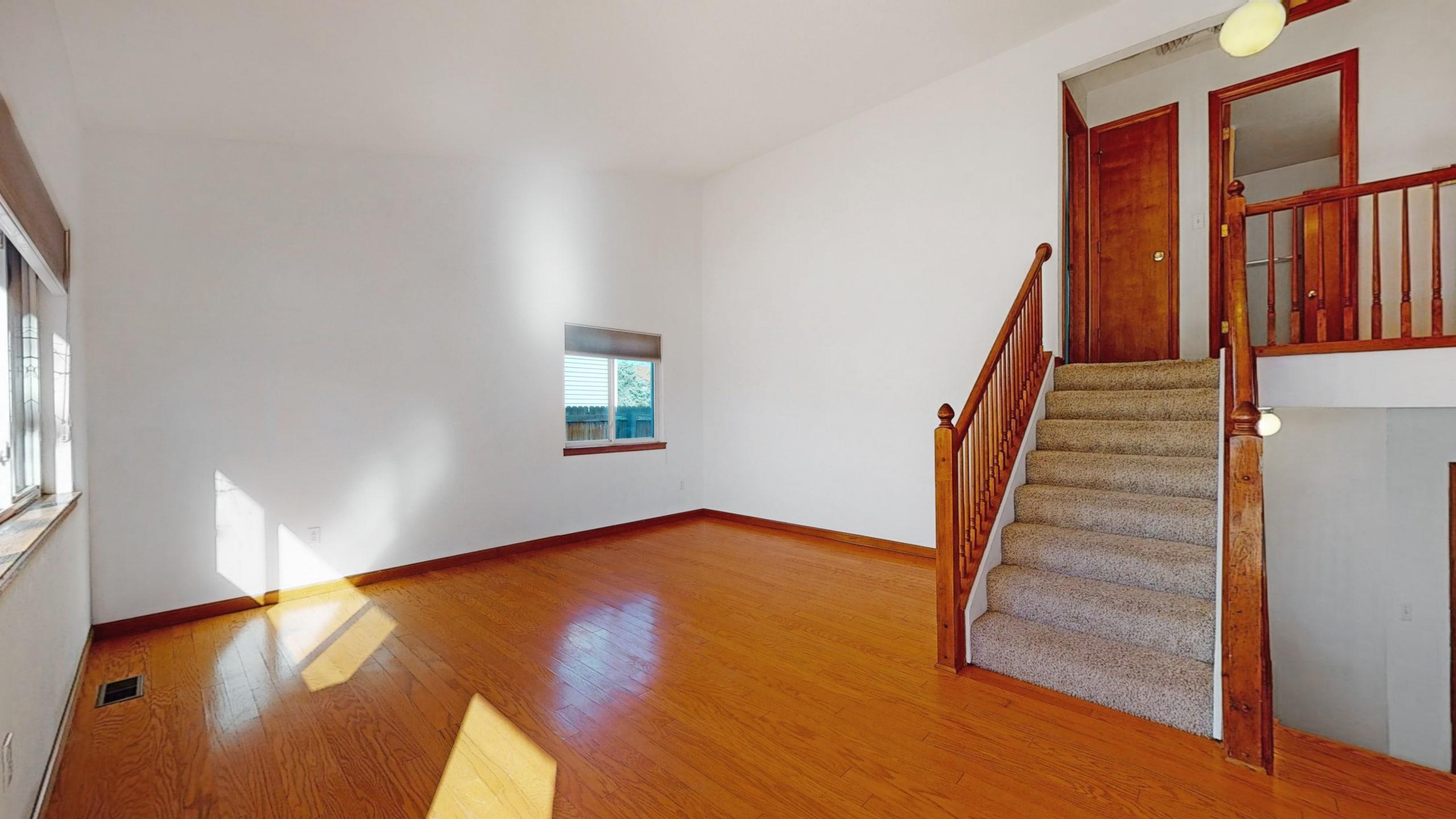 Wood floors, wood banister, white walls, large window