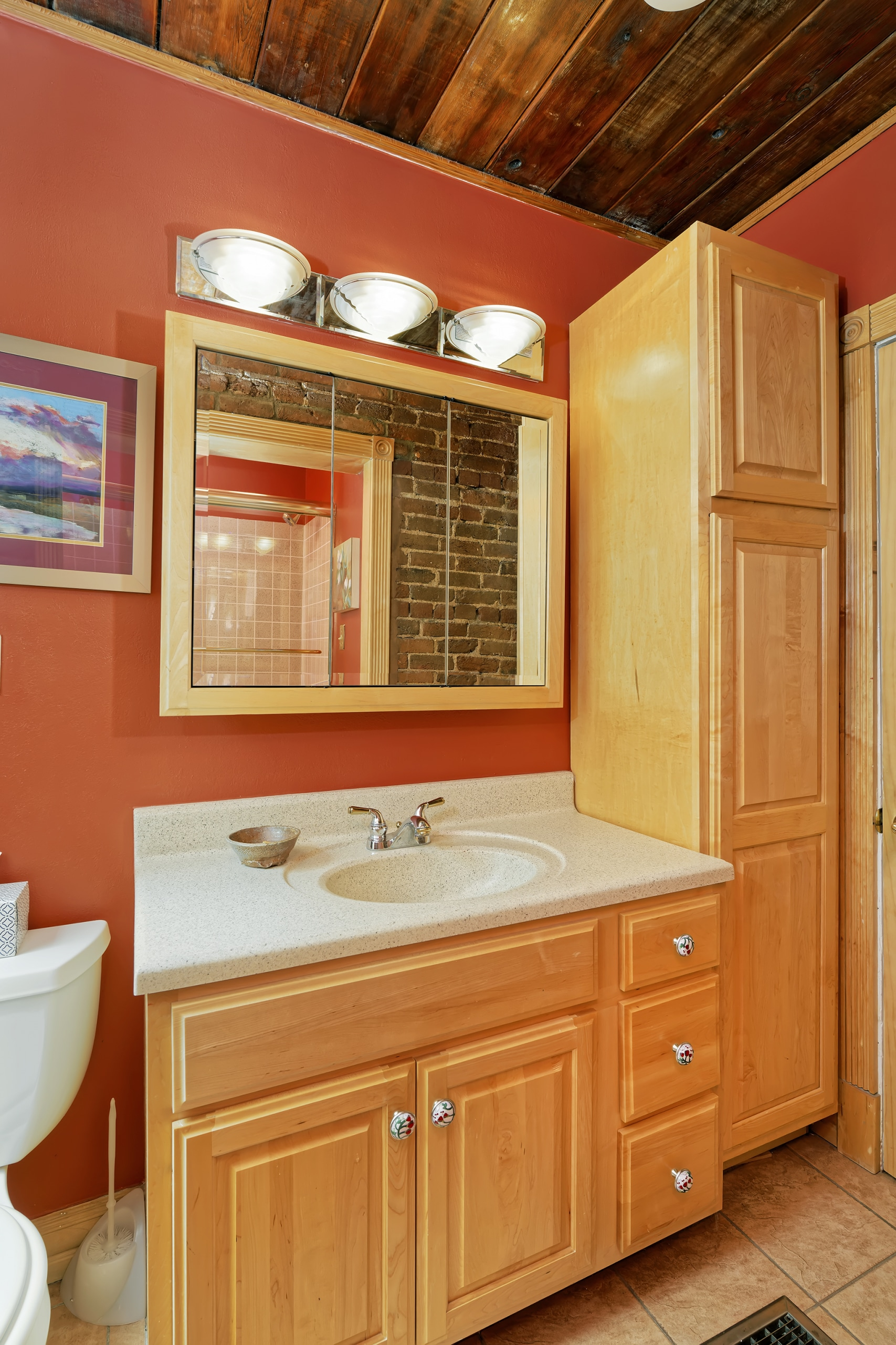 Bathroom with exposed red brick and oak cabinets