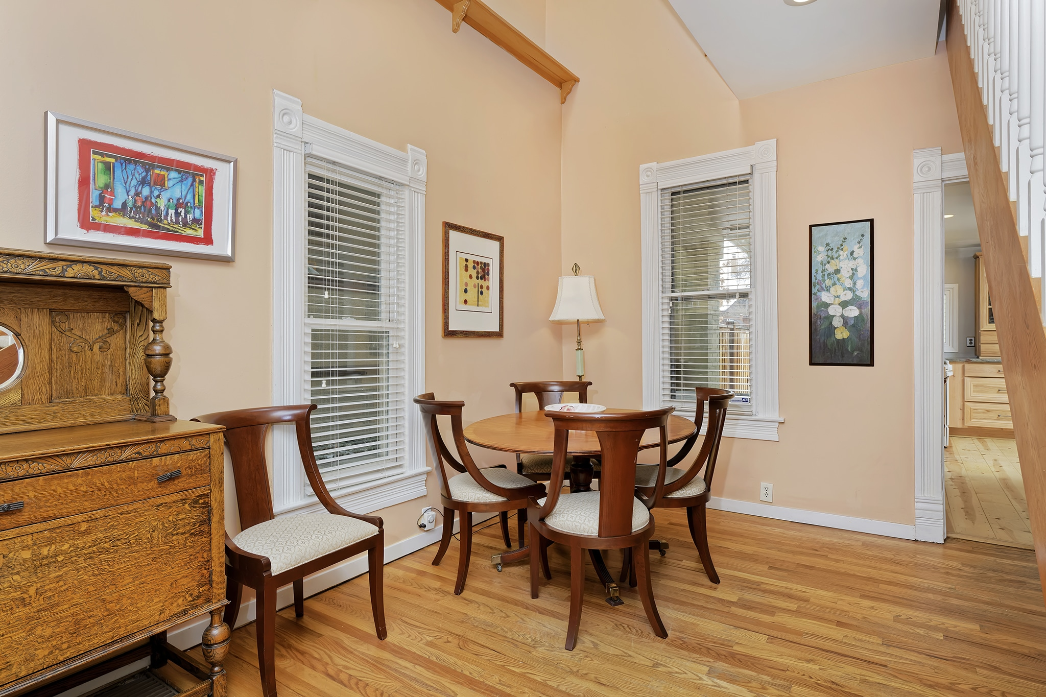 Dining room area with open vaulted ceiling, natural light, oak floors