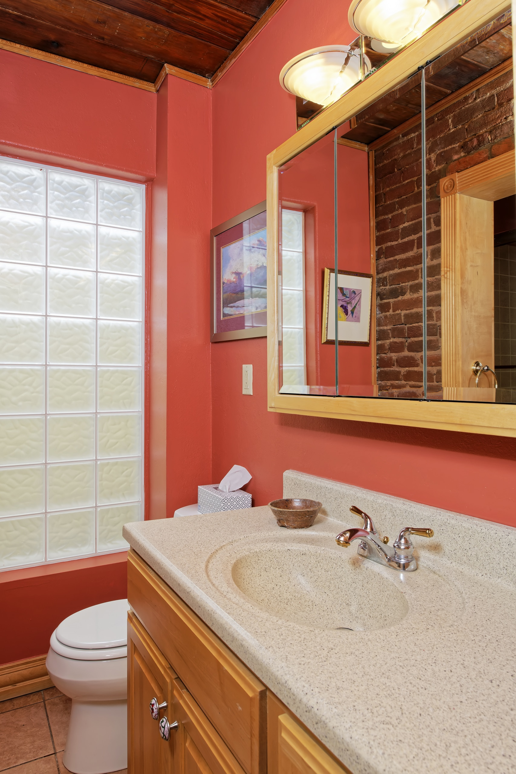 Main floor bath with salmon walls, glass block tile, wood ceiling
