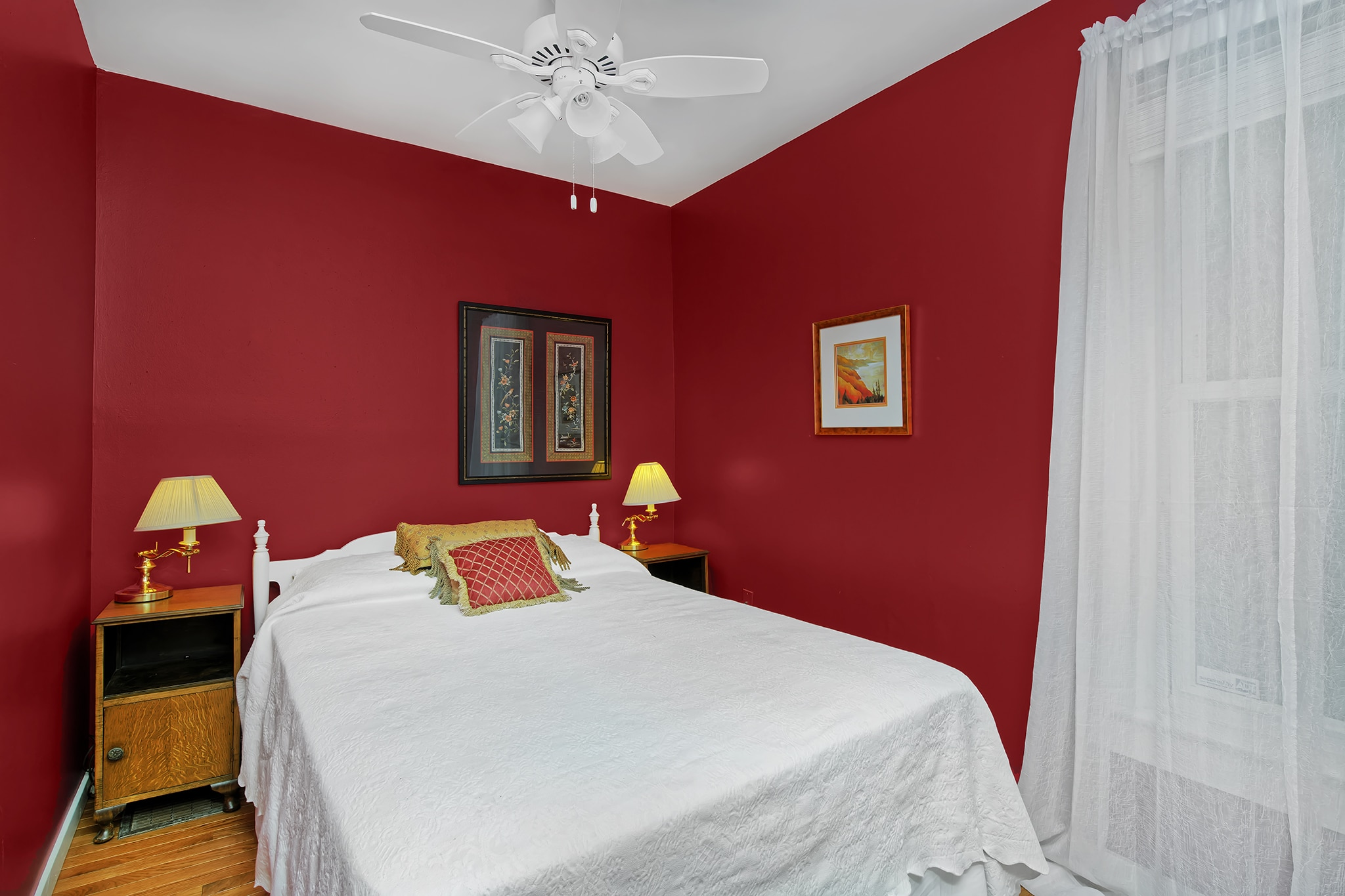 Washington Park Home With Extra Bedroom on main floor, red walls, white ceiling with ceiling fan, hardwood floors