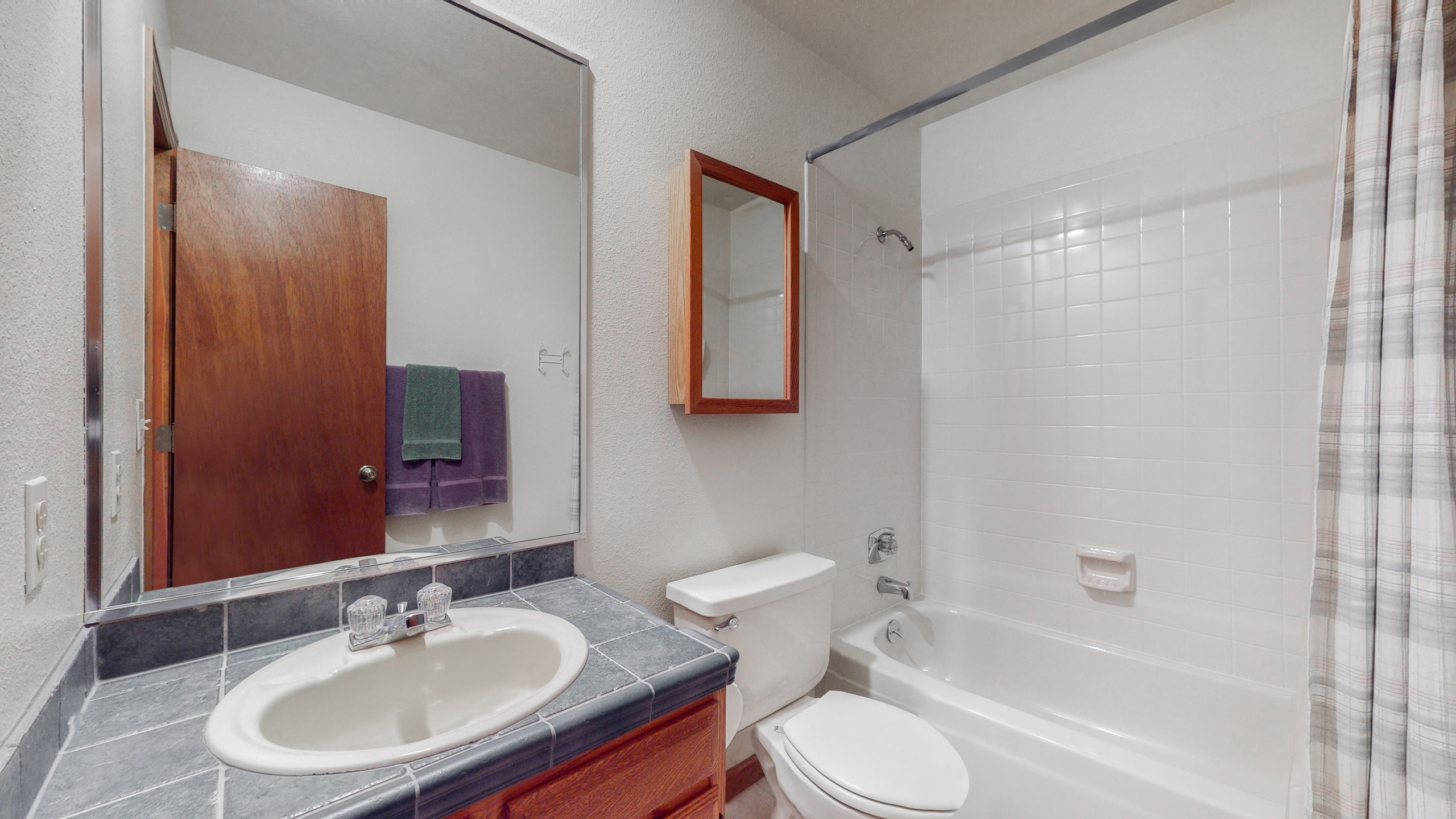 Full bathroom upstairs with tile counters and tile shower