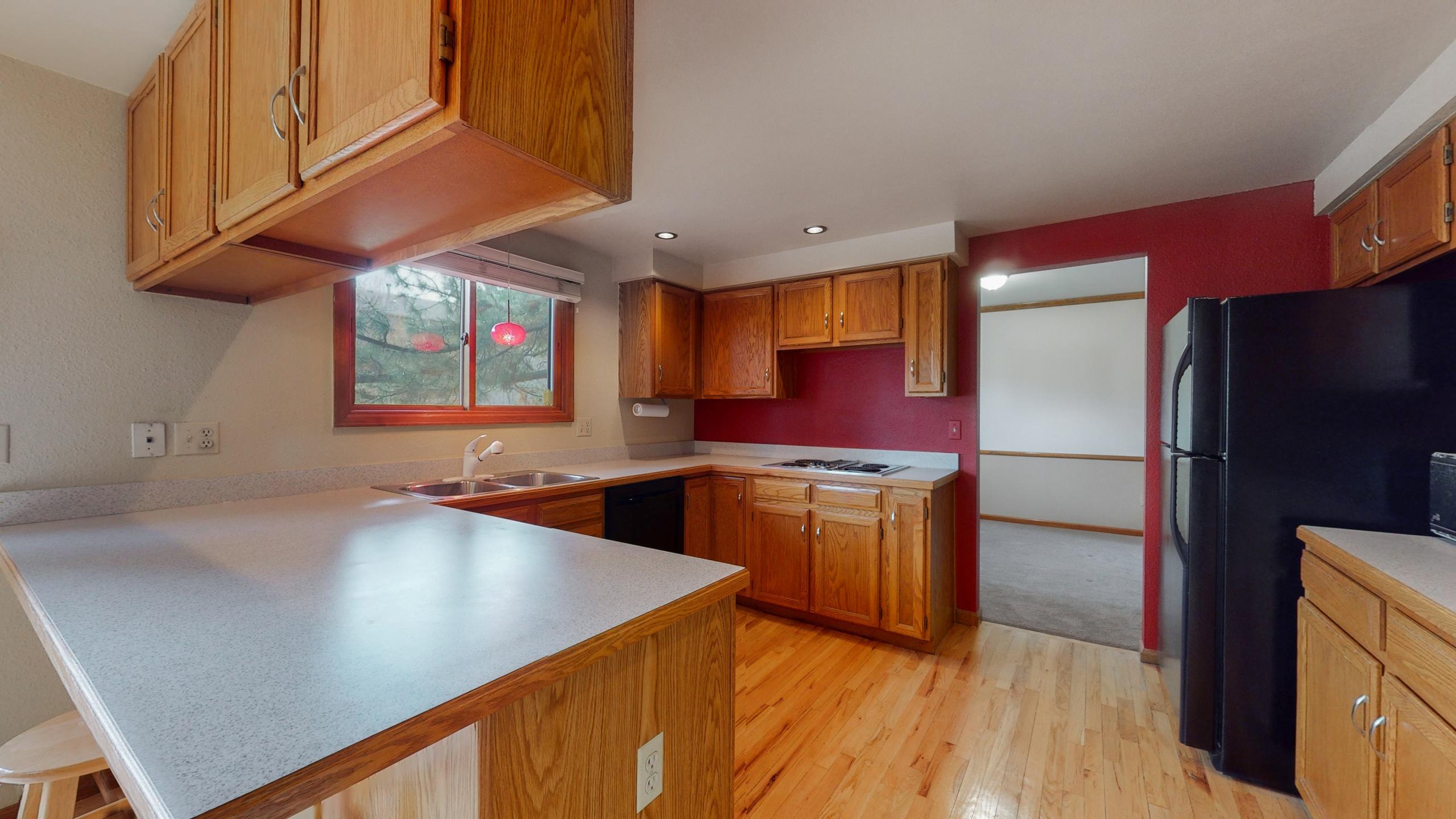Kitchen with oak cabinets, hardwood floors, black appliances