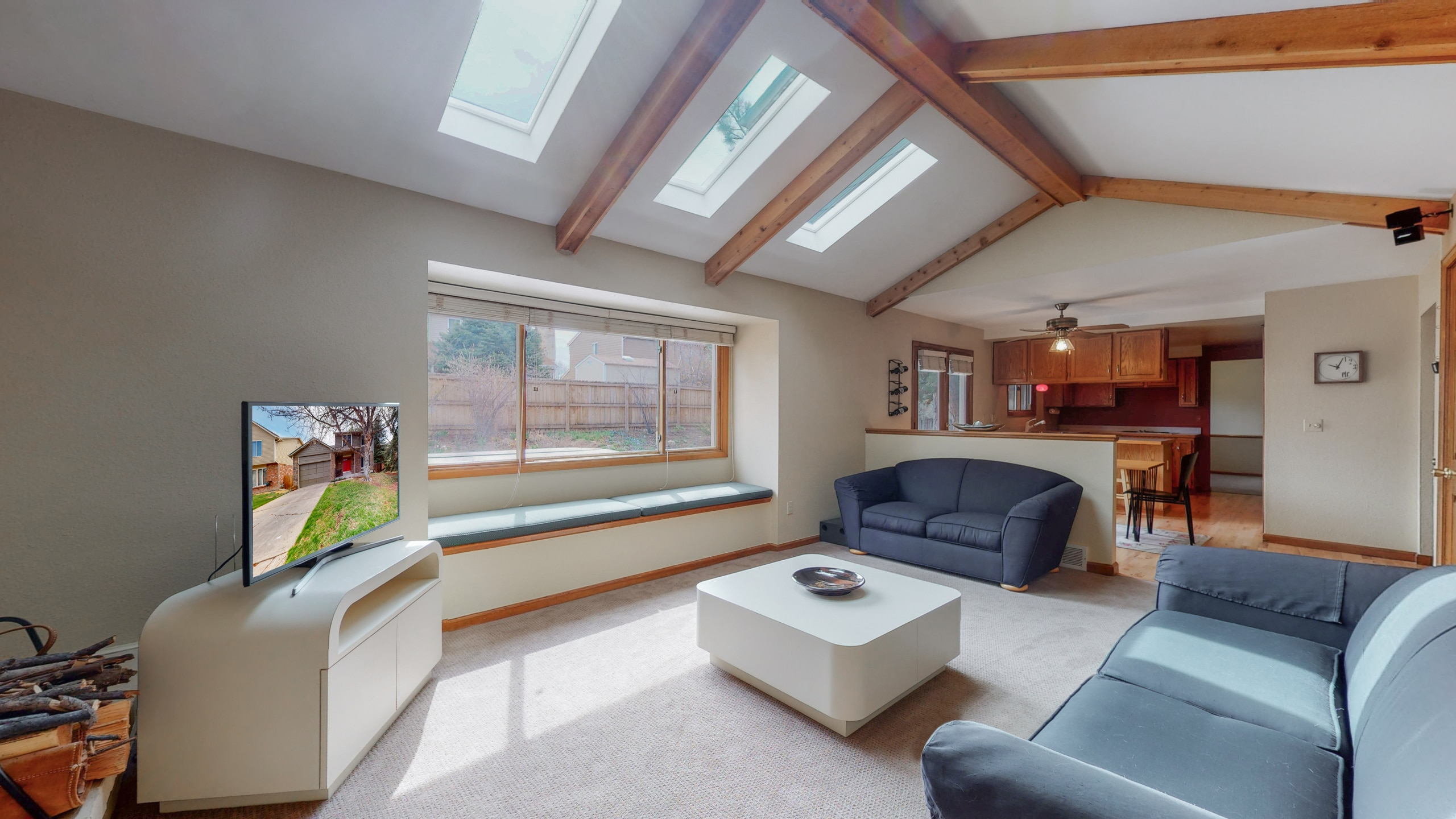 Natural wood beams highlighted by skylights in living room