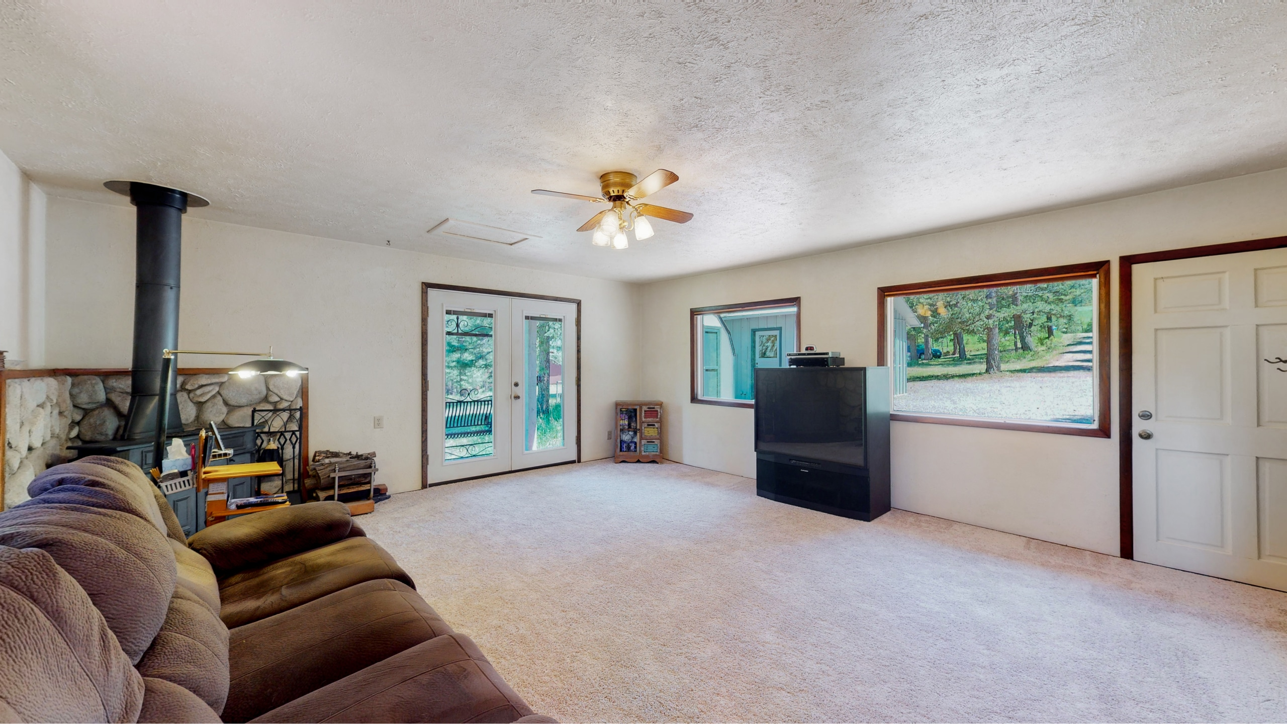 Large family room with wood fireplace and big windows in Evergreen, CO