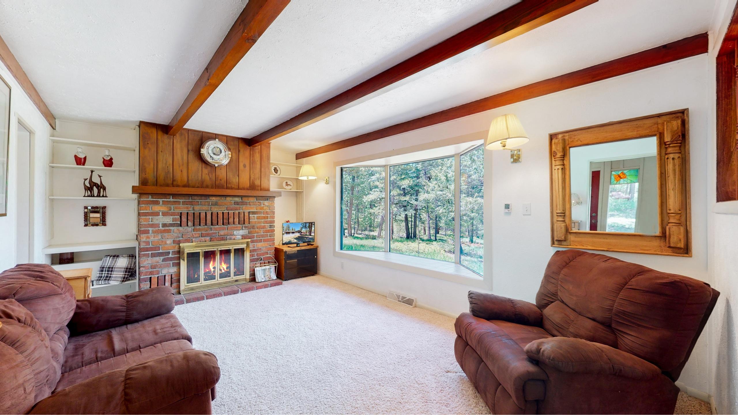 Living room with big bay windows and wood beams
