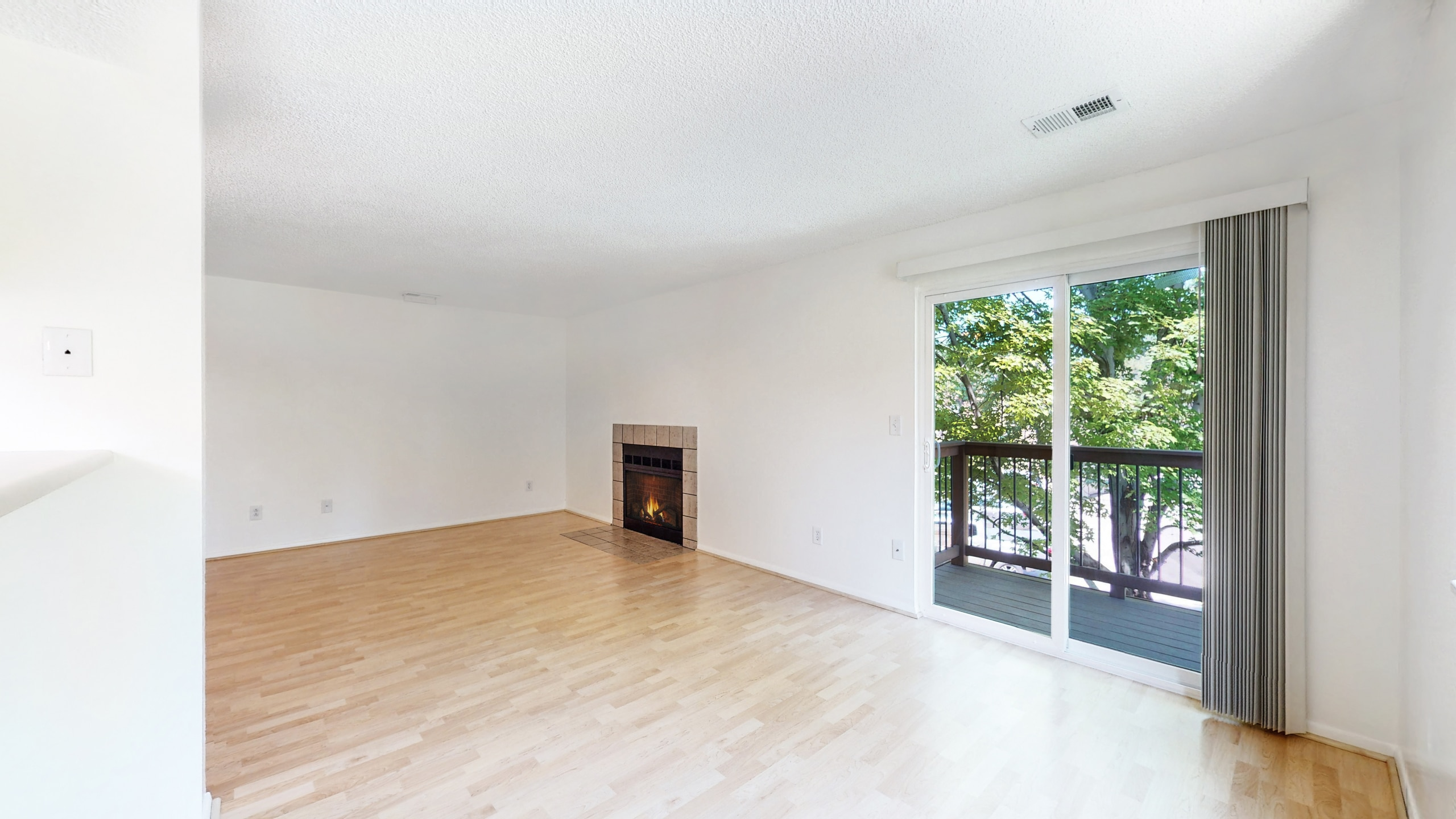 Living Room Highlighting Private Balcony and wood fireplace
